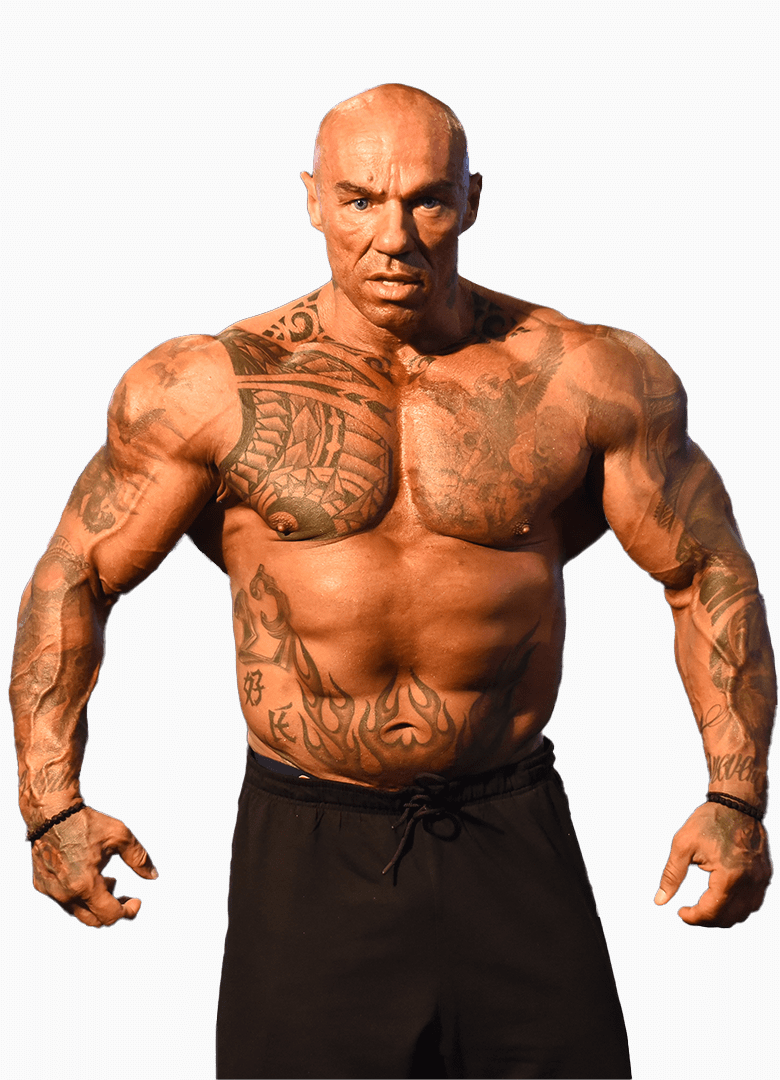 Tose Zafirov in black pants showcasing his body, tattoos and muscles while staring directly at the camera