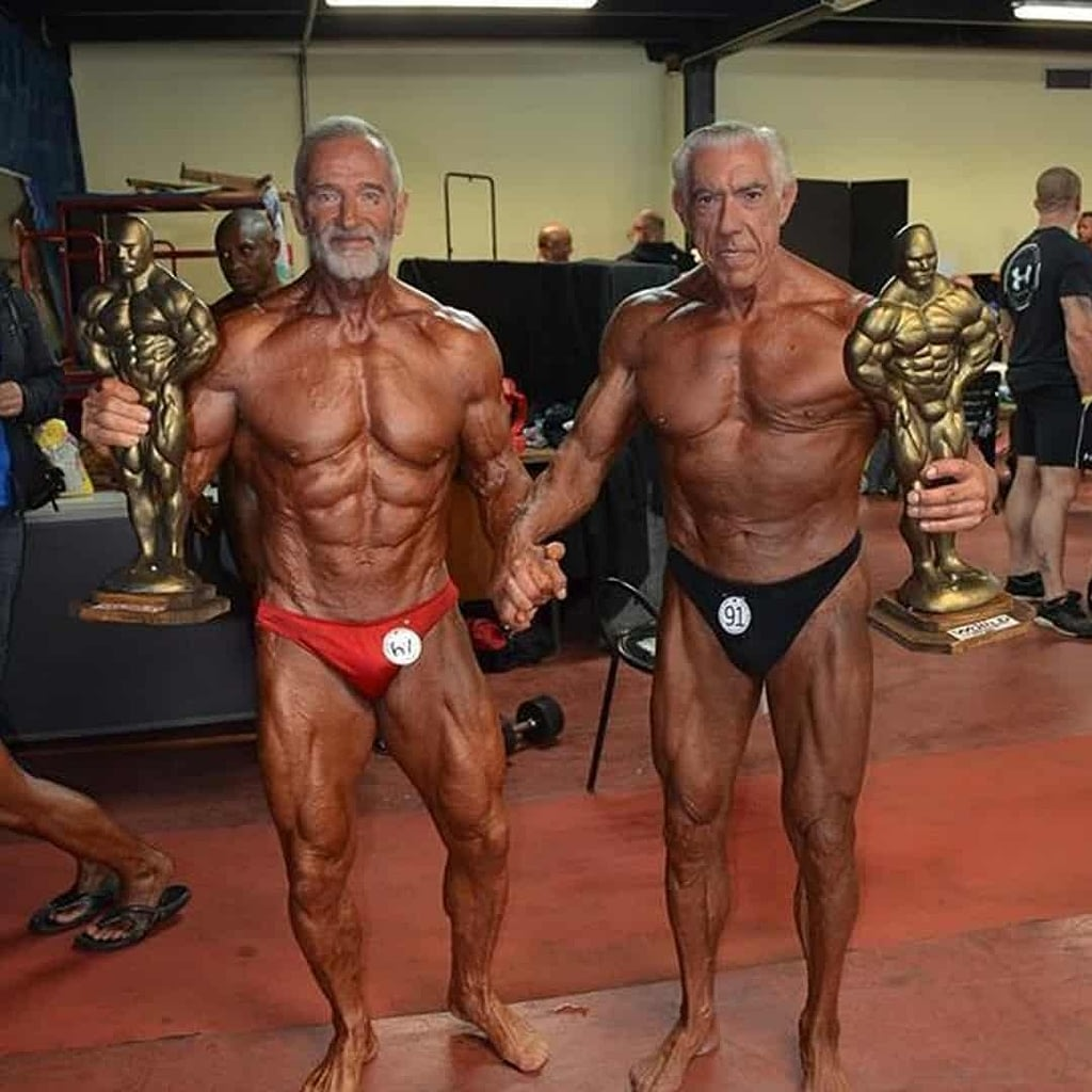 Petar Celik at an older age fit and buff filled with muscles in a backstage of a competition, wearing a red trunks. He is holding an award in one of his hands. With the other hand he is holding the hand of his friend who is staying next to him and holding and award too.