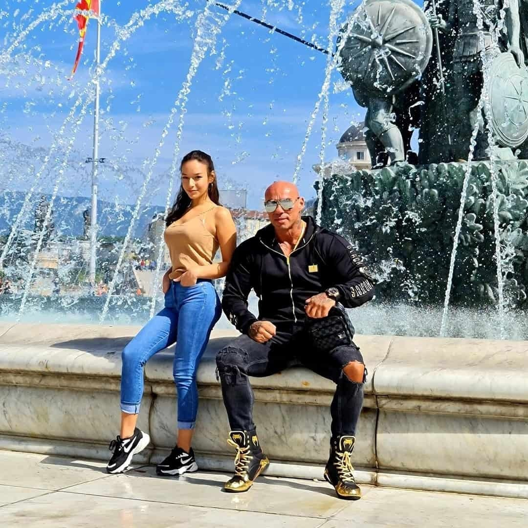 Tose Zafirov in a black sweatshirt and grey jeans, with sunglasses on his eyes, next to his daughter. She is wearing crème t-shirt and blue jeans. They are in front of a huge fountain on the City Square in Skopje.