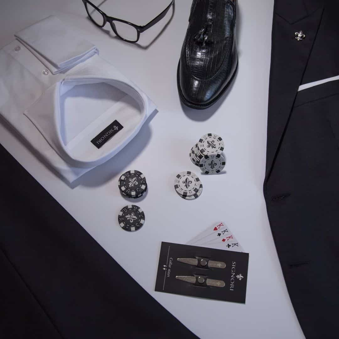 An image of an entire Suit setup from Signori in Black on a white background. Together with black, elegant shoes, glasses and some poker chips.