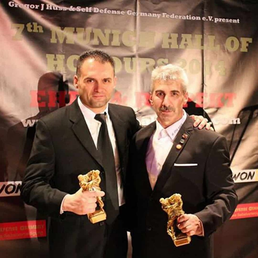Ivica Aleksovski, in a black suit, standing next to another men, holding an award in his hands.