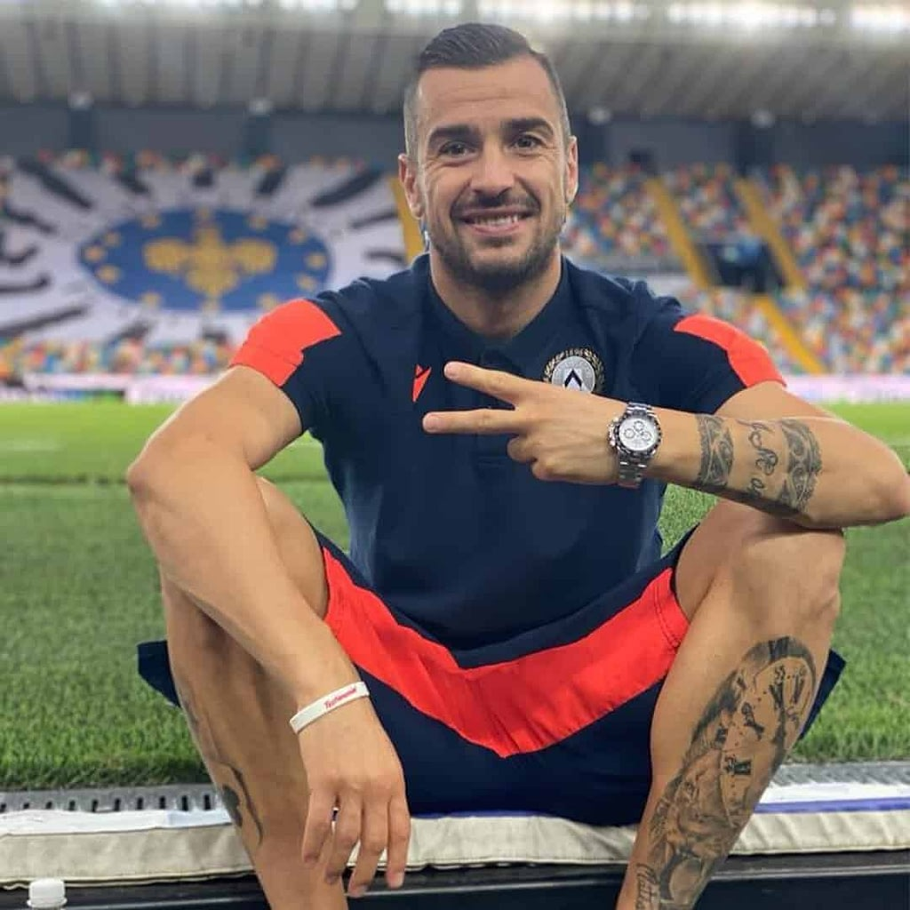 Ilija Nestorovski sitting on a football playground, and making piece symbol with two of his fingers. He is weaing navy blue jersey with orange details.