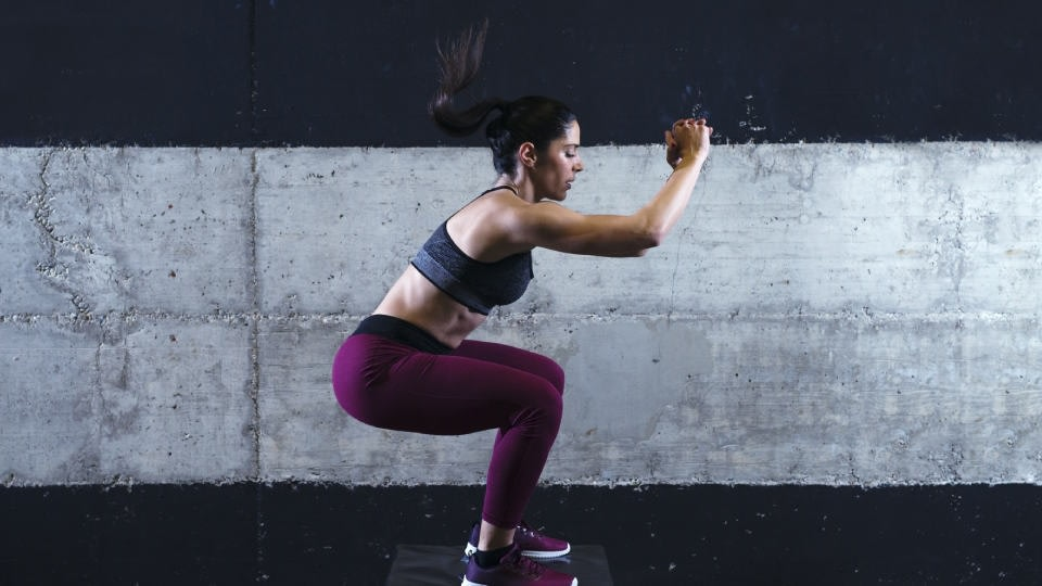 A woman training outside, doing squat jumps while wearing dark grey sports bra and purple leggings.
