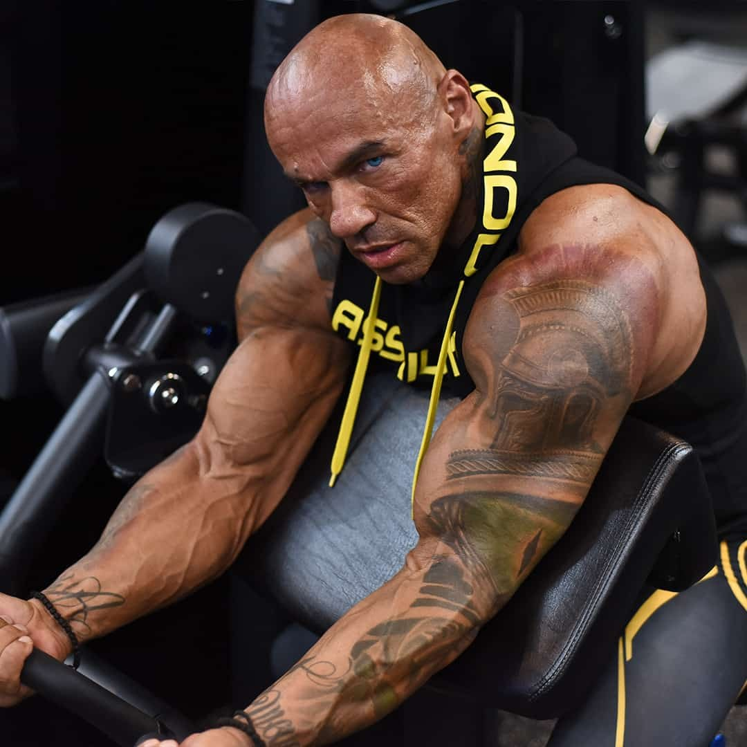 Tose Zafirov training his biceps muscles while staring at the camera, he has a tattoo on his arm and he is wearing black t-shirt with yellow details.