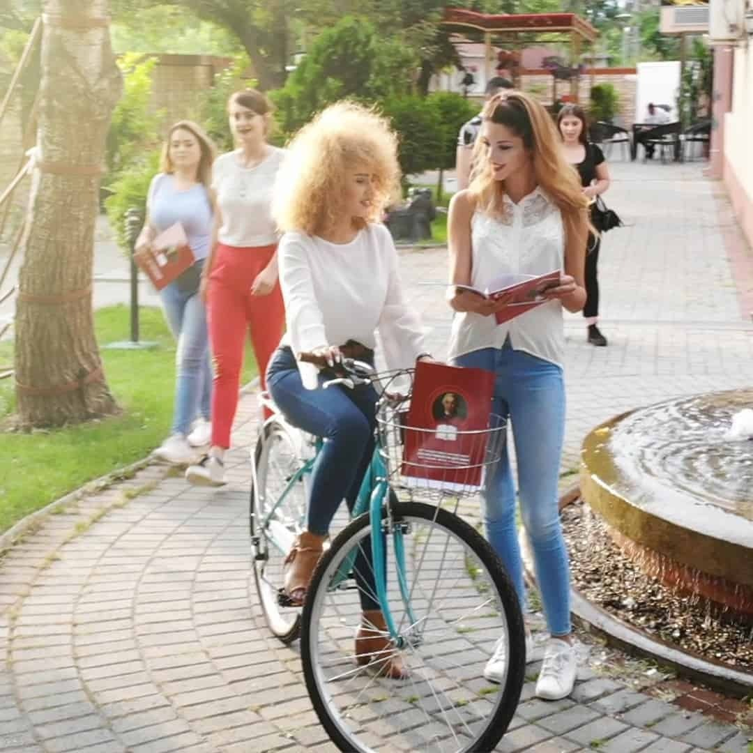 A woman in jeans and white shirt, riding a bike on the campus of International Slavic University G. R. Derzhavin, while another girl, with a book in her hands, wearing a jeans and white shirt is standing next to her and they are discussing something. There ae some other people behind them too.