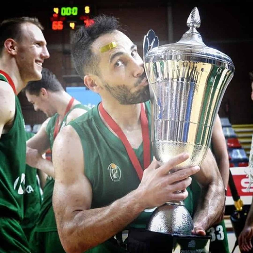 Rok Stipcevic wearing a green jersey, holding a trophy.