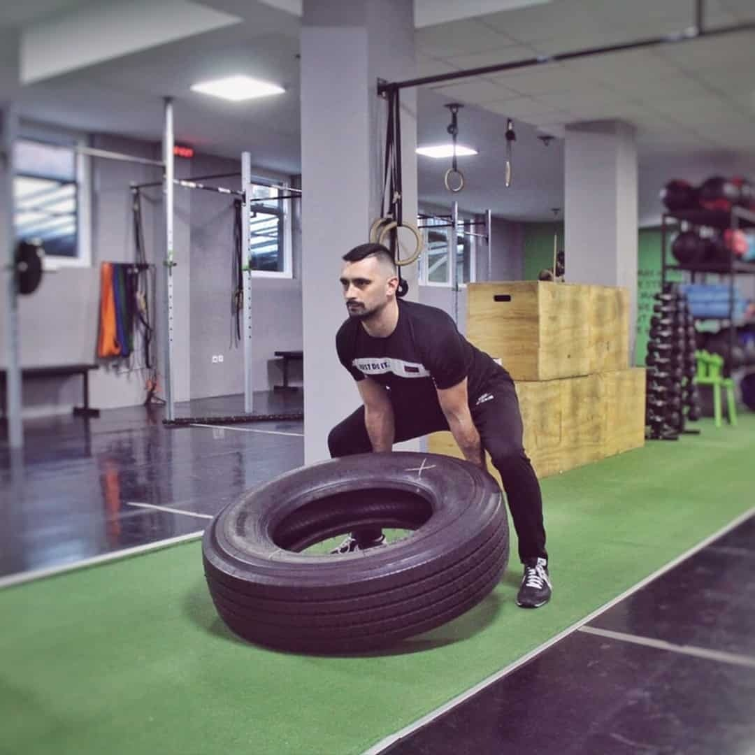 Aleksandar Mandzukovski lifting a tire at the gym in order to build his strength. He is wearing black t-shirt with white details and black sweatpants.