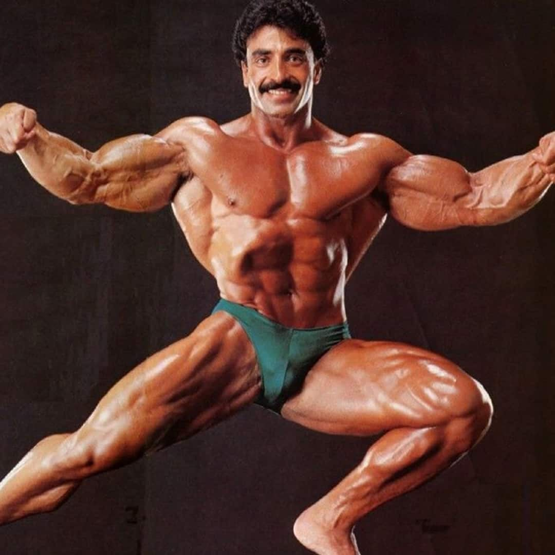 An image of Samir Bannout, while flefing his muscles and wearing green trunks.