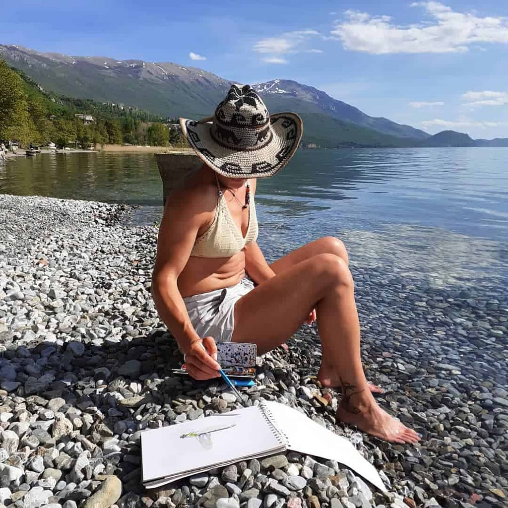 Ilina Arsova next to the lake, on a beach, while painting. She is wearing a hat and bikini, toghether with white shorts.