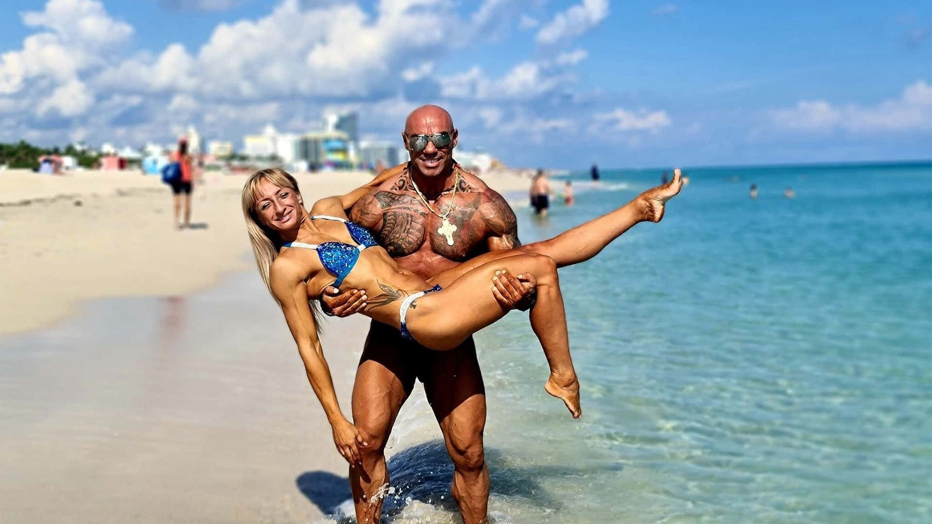Tose Zafirov and Gabriela Zafirova at the beach where Tose is holding Gabriela in his hands. Gabirela is wearing blue bikini and she is smiling, while Tose is wearing sunglasses on his eyes, and a big golden necklace .