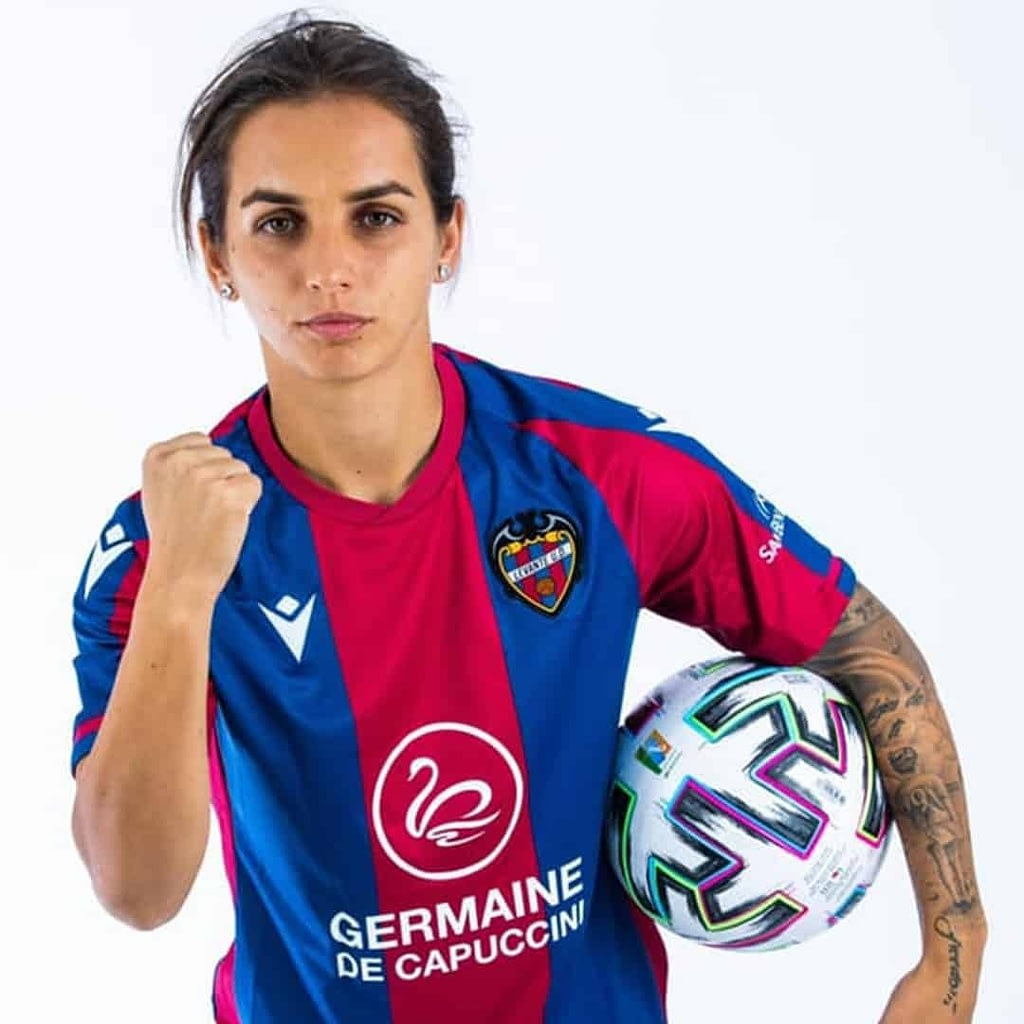 Natasa Andonova in a Levante jersey, holding a football in her hand and staring straight at the camera on a white background.