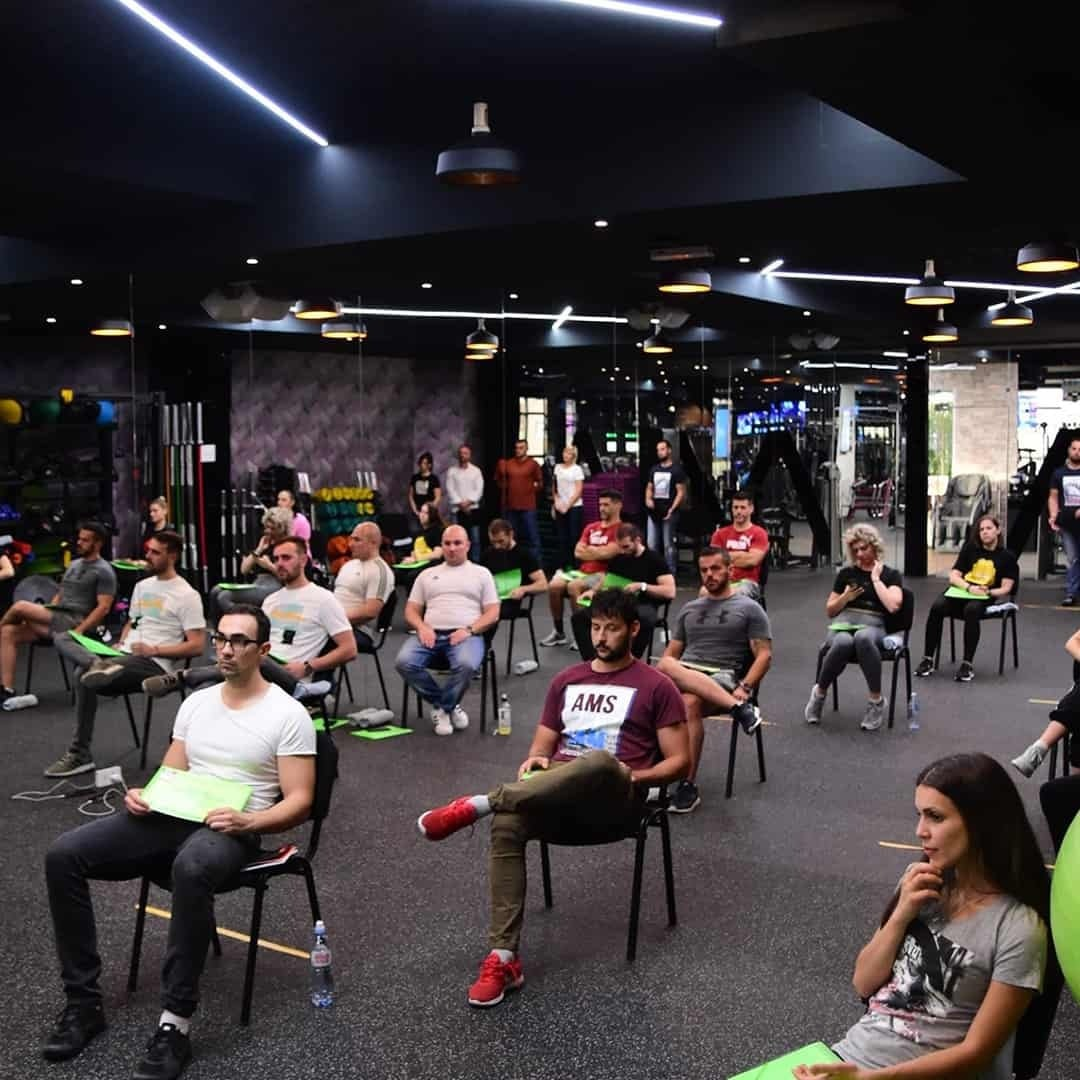 An image of the attending students of the Fit Biz Academy sitting on black chairs in the Pulse Fitness Center.