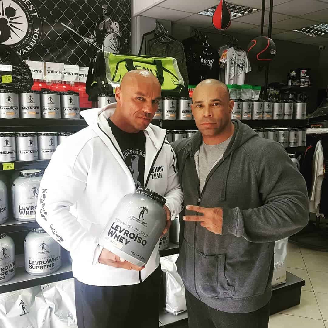 Tose Zafirov and Kevin Levrone, with a shelf of proteins in the background, Kevin is hugging Tose, while Tose is holding protein in his hands.