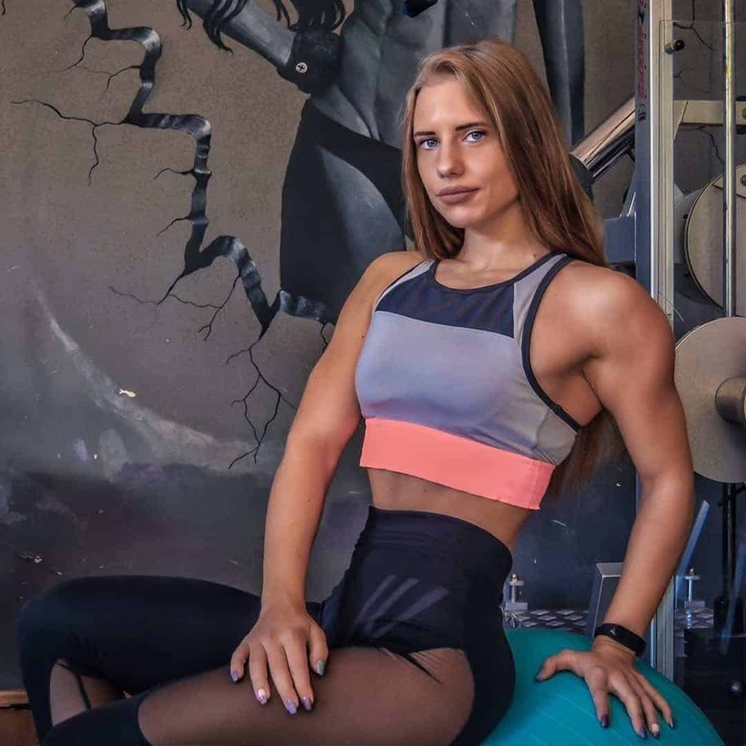 Sara Stojanoska on a photoshoot at the gym sitting on a blue, training ball while wearing grey sports bra with pink details and black leggings.