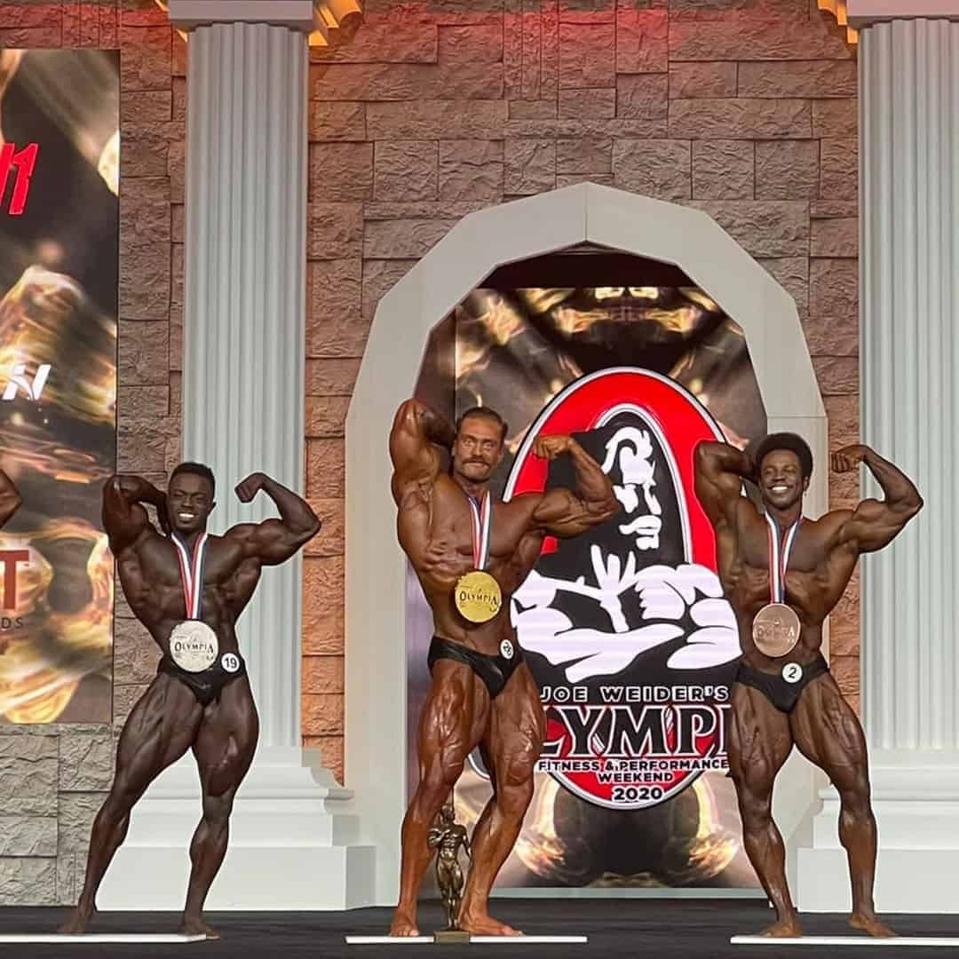 An image of the bodybuildeers who won the first three places on the Mr. Olympia Competition. They are on stage, with the medals on their necks.