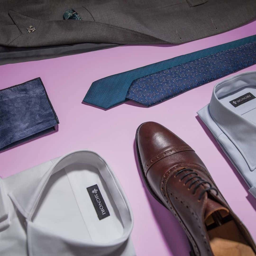 An image of white shirt and light grey shirt, two ties in navy blue and turquoise colour, with dark grey suit, and dark brown shoes. All those things are on a pink background.