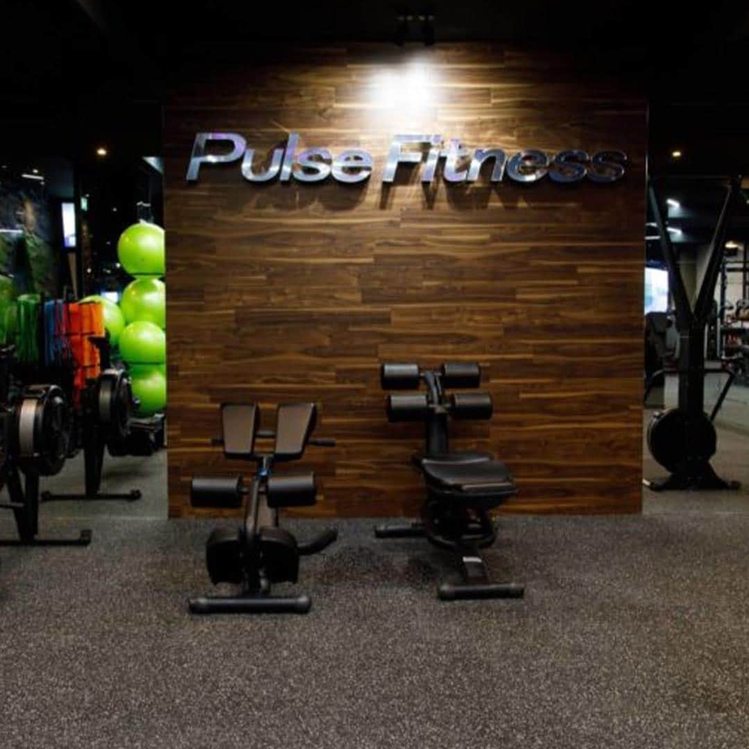 An image of the Pulse Fitness Center, with its logo on the wall, and some equipment.