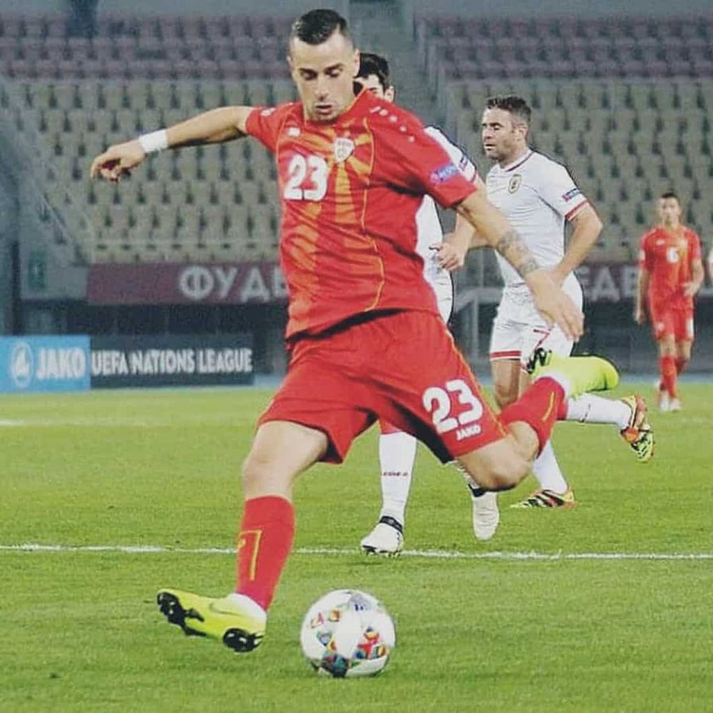 Ilija Nestorovski while playing a match for the National Macedonian Footabll team. He is wearing red jersey with yellow sun on it.