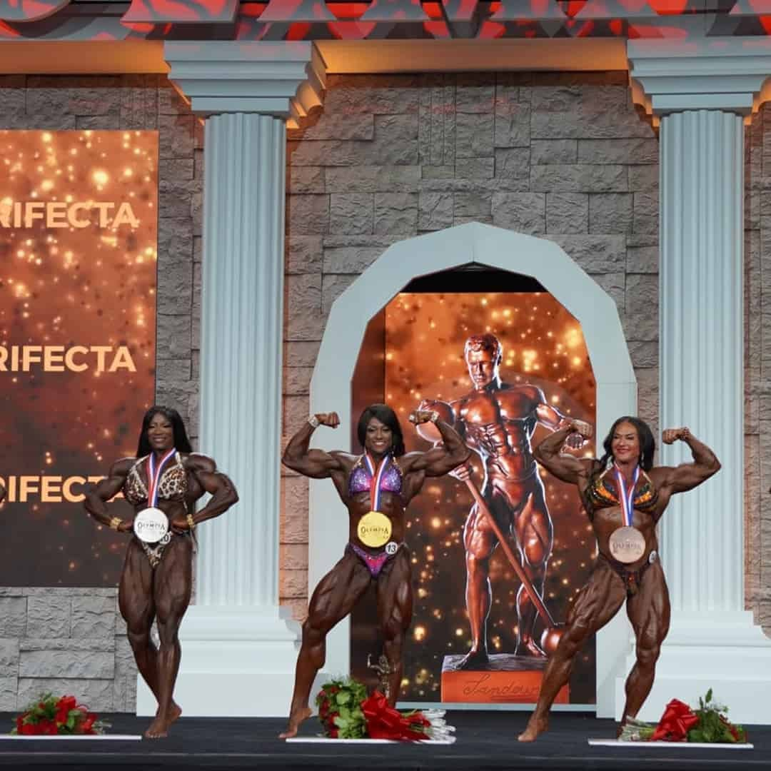 An image of the three women who won the first three places on Mr. Olymipa. They are on the stage with the medals on their neck, and they are flxing their muscles.