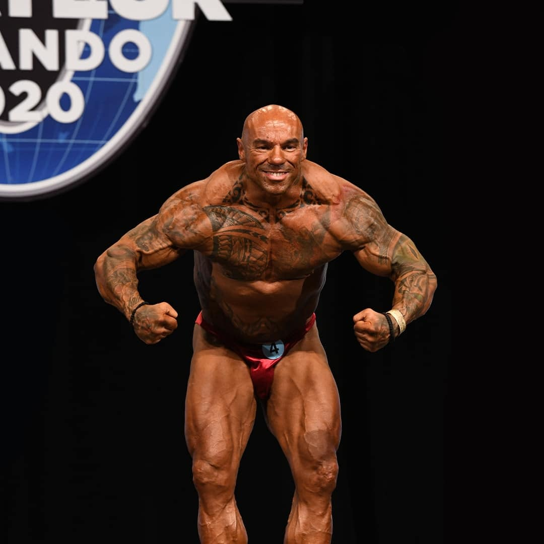 Tose Zafirov flexing his muscles on stage on Mr. Olympia Orlando 2020. He is wearing red trunks.