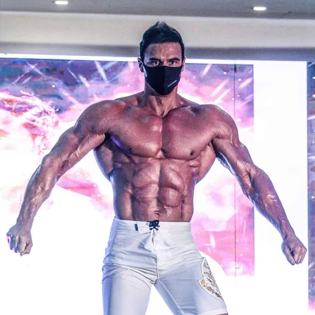Branko Teodorovic wearing white pants and flexing his abs well well as other muscles at a competition. He is also wearing a black mask on his face.