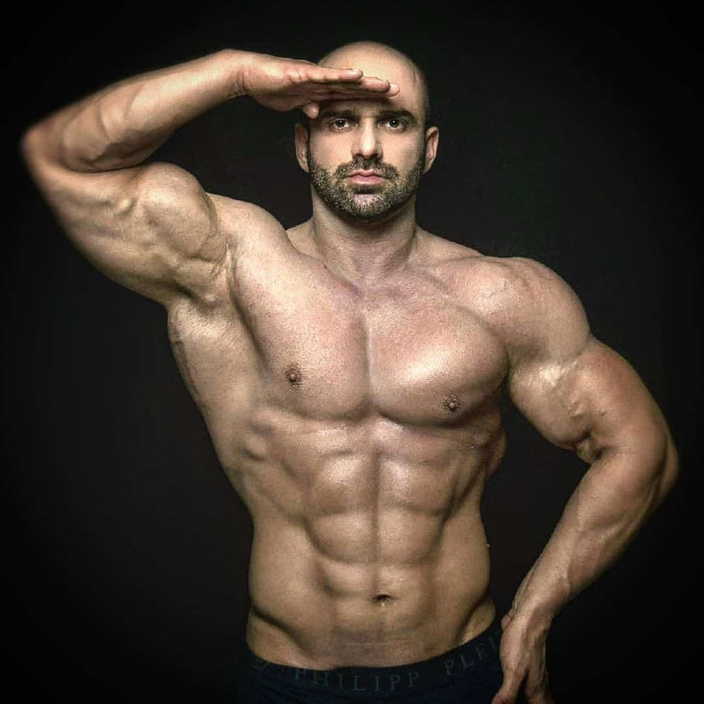 An image of Lepomir Bakic, a famous, professional bodybuilder. He is looking right at the camera, with one hand on the head and the other on his hip. Without a t-shirt, he is showing his strong, flexed muscles, biceps, and abs.
