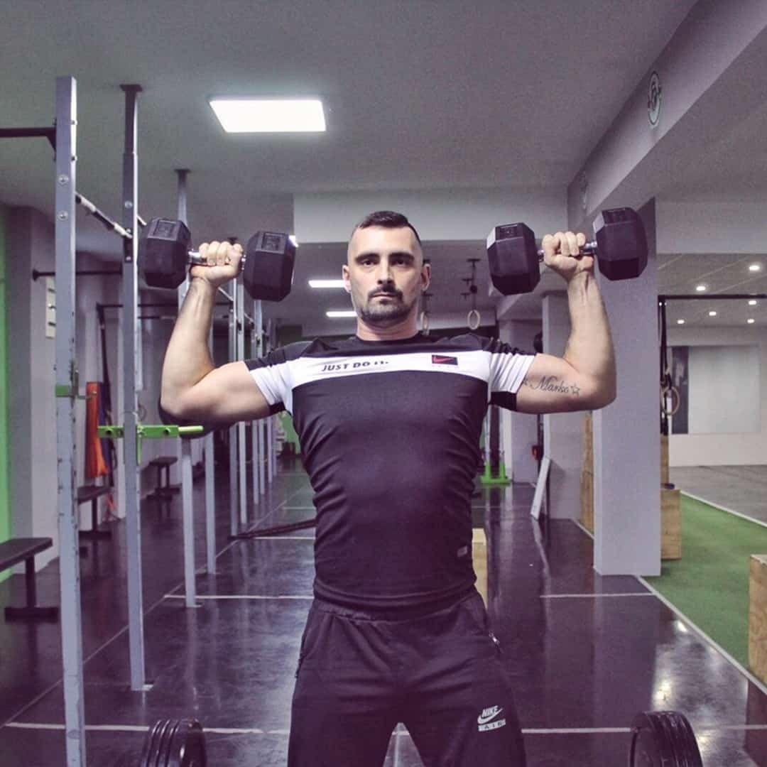 Aleksandar Mandzukovski lifting two dumbbells up with his hands in order to train his shoulders. He is wearing black t-shirt with white details and black sweatpants.