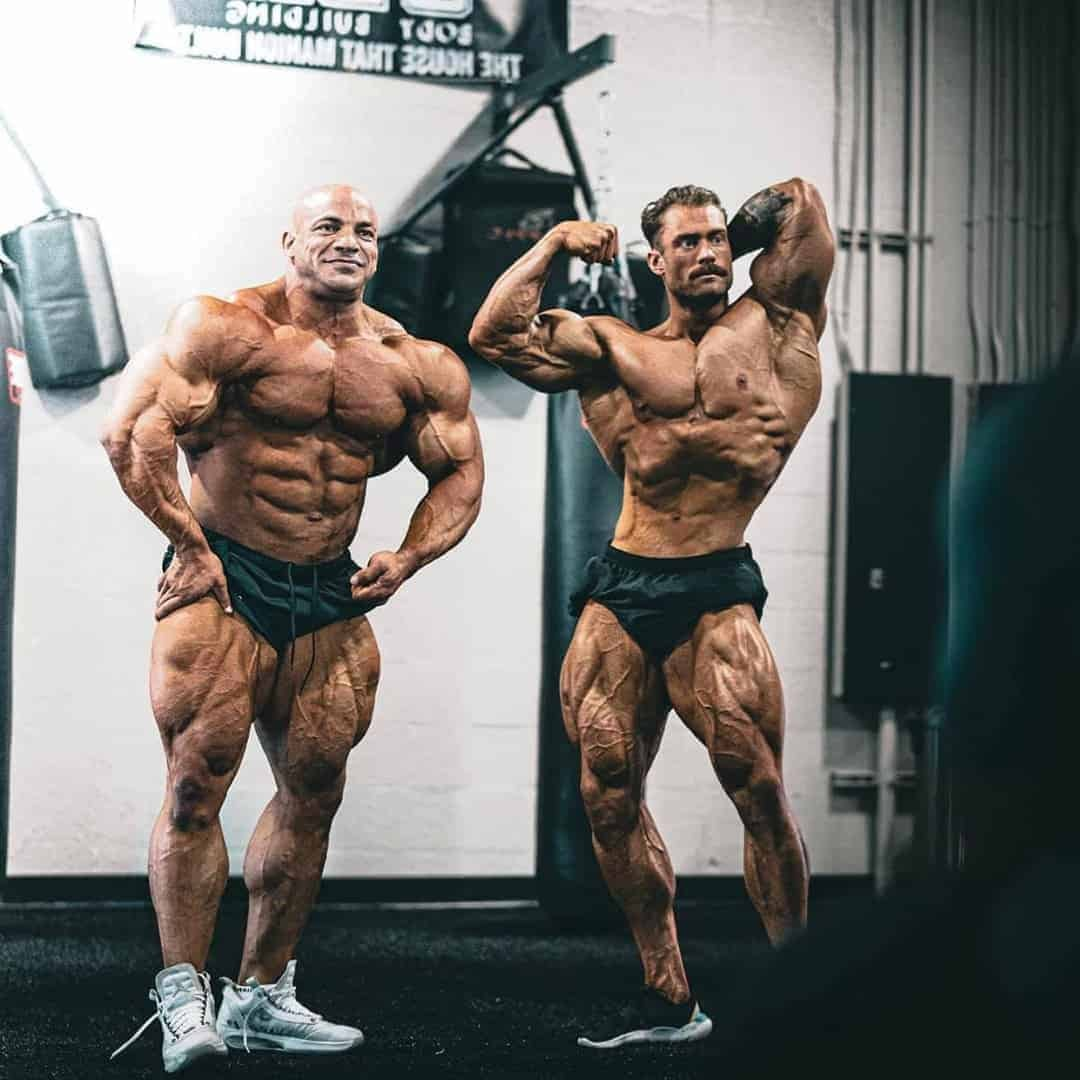 Chris Bumstead and Big Ramy in a gym. They are both flexing his muscles while they are not wearing t-shirts.