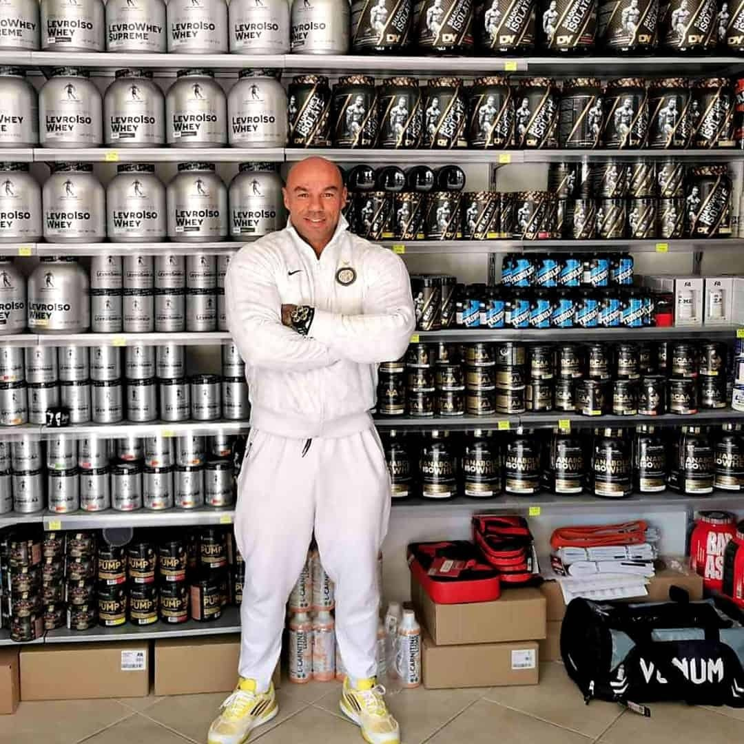 Tose Zafirov at a supplement store standing in front of Kevin Levrone Signature Series supplements on a shell. He is wearing white hoodie and white sweatpants.