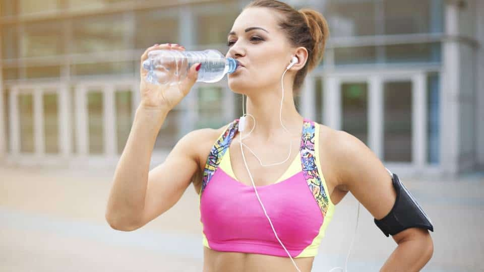 An image of a woman drinking water from a bottle after a workout. She is in front of a building, wearing pink sports bra with yellow details, and black phone holder on her hand.