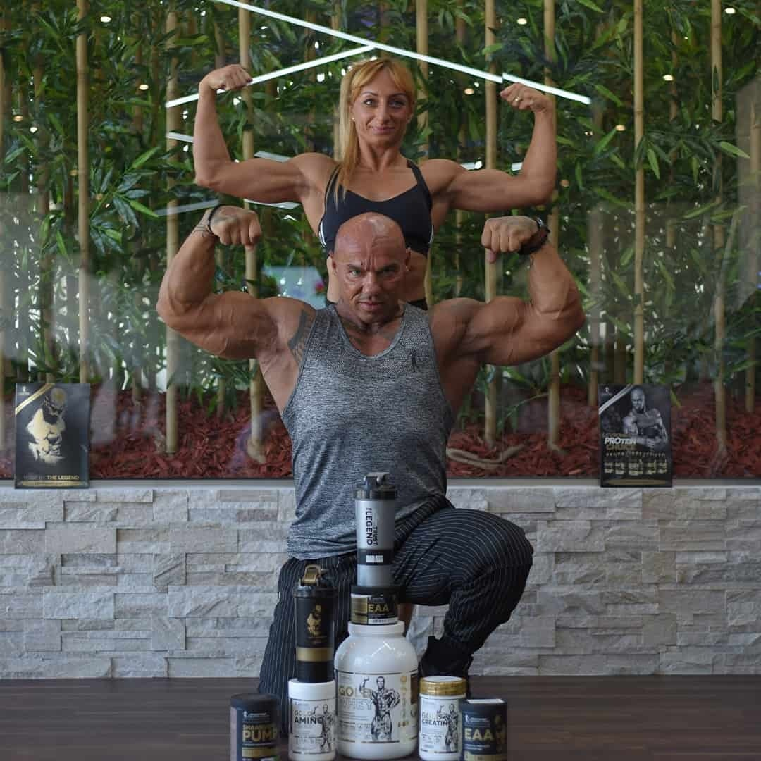 Tose Zafirov and Gabriela Zafirova flexing their biceps muscles in front of Kevin Levrone supplements. With plastic bamboo trees in the background.