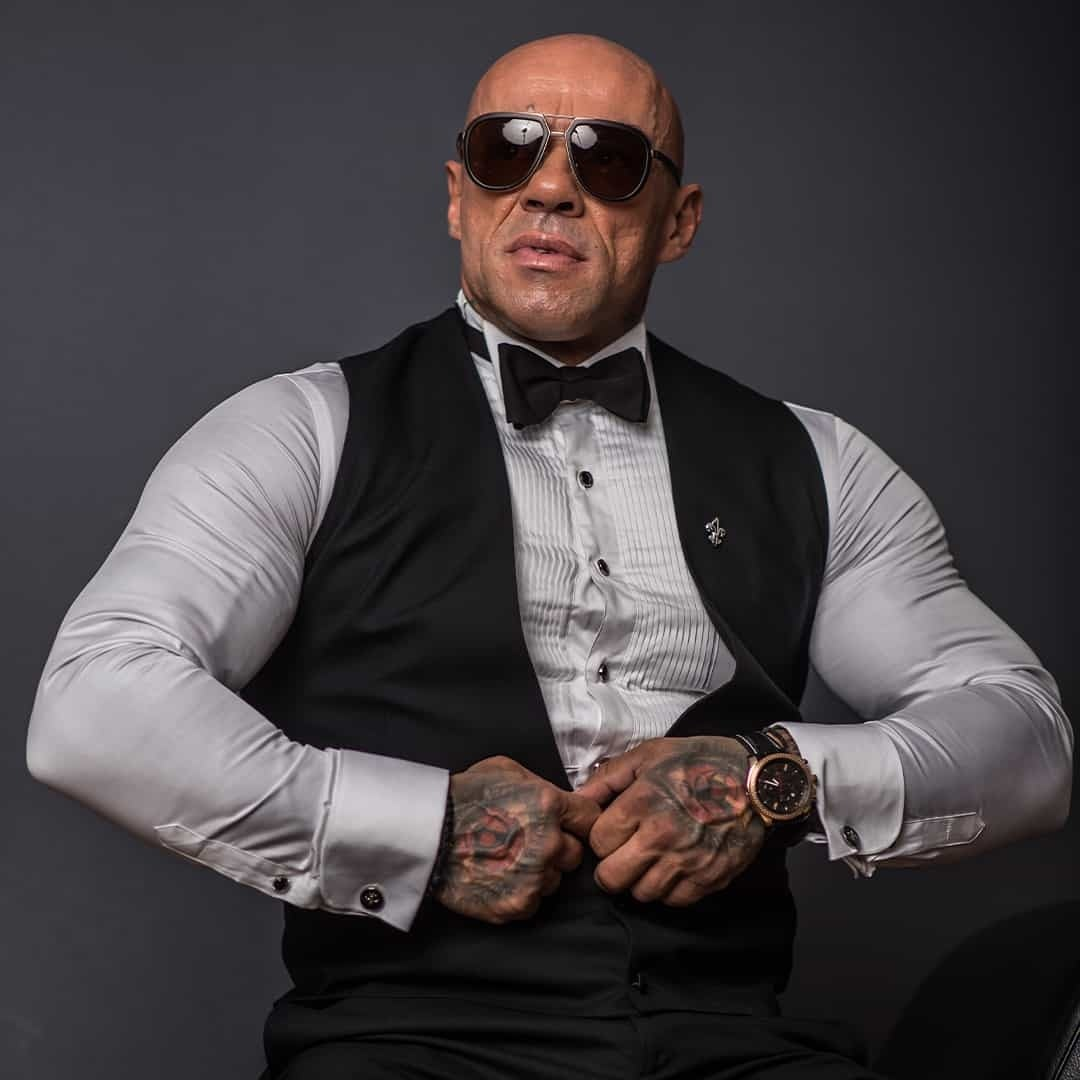 An image of Tose Zafirov wearing a shirt and vest from Signori, and sunglasses on his eyes while posing on a grey backgound.