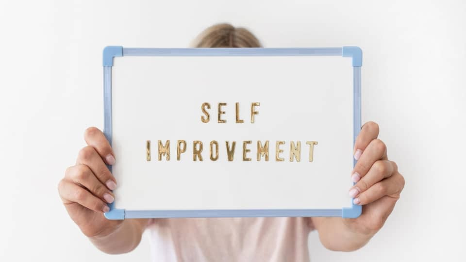 An image of a girl holding up a self improvement sign in front of her head, standing in front of a white background.