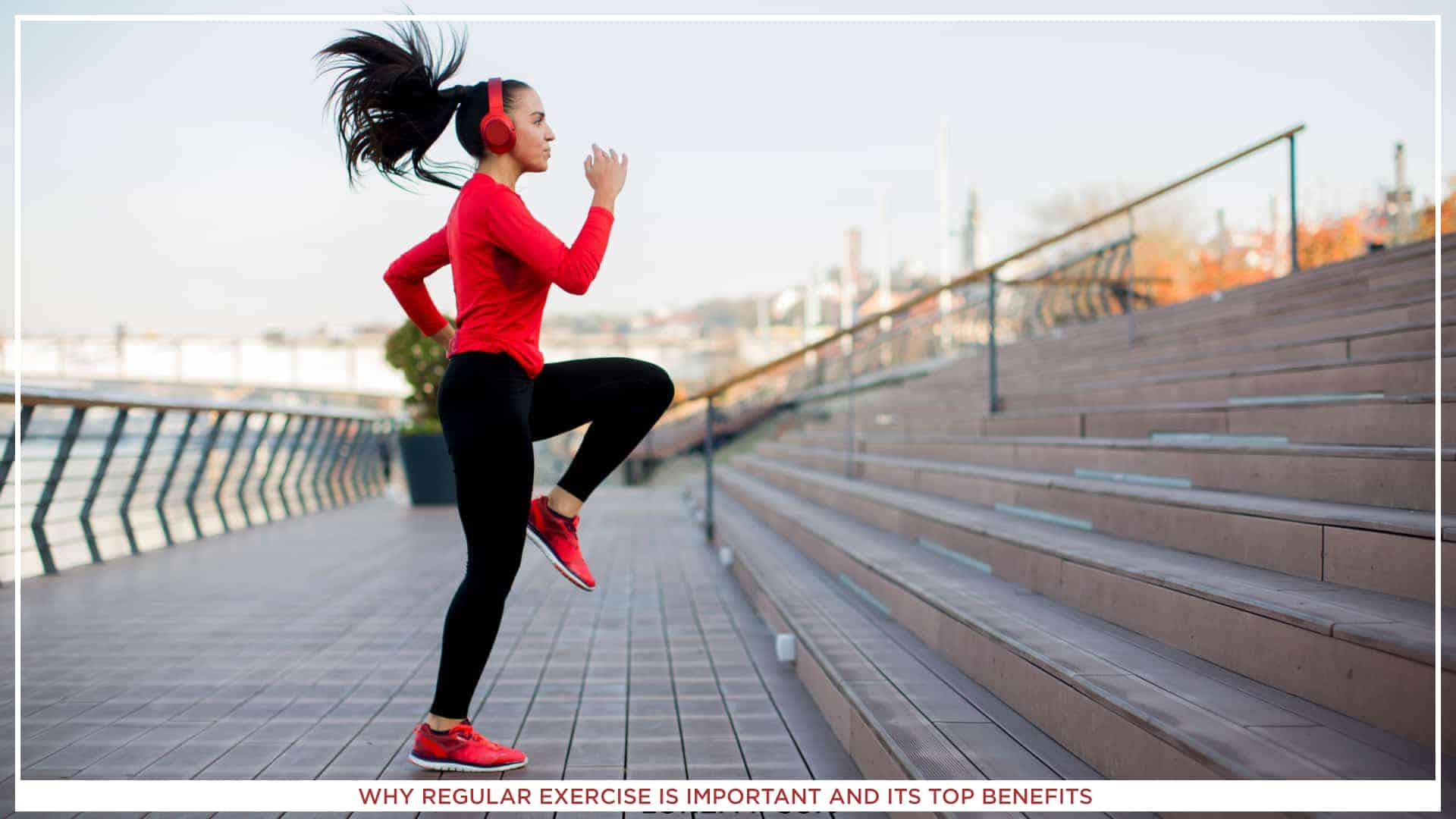 A girl wearing red hoodie, black leggining and red sneakers while doing regular exercise outside, on a stairs. She is also wearing red headphones one her ears.