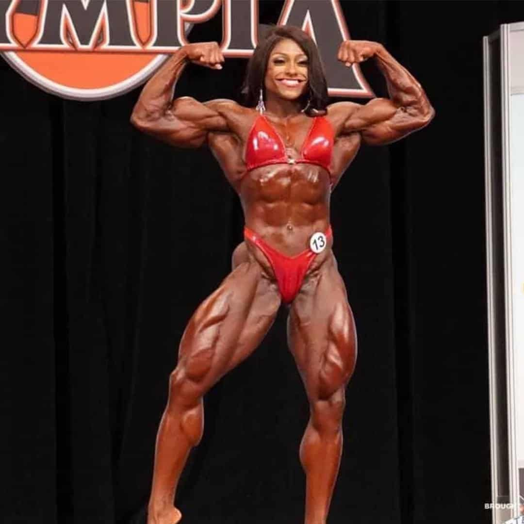 An image of Andrea Shaw on the Mr. Olymipa Competition stage. She is smiling while flexing her muscles and she is wearing red elegant bikini set.