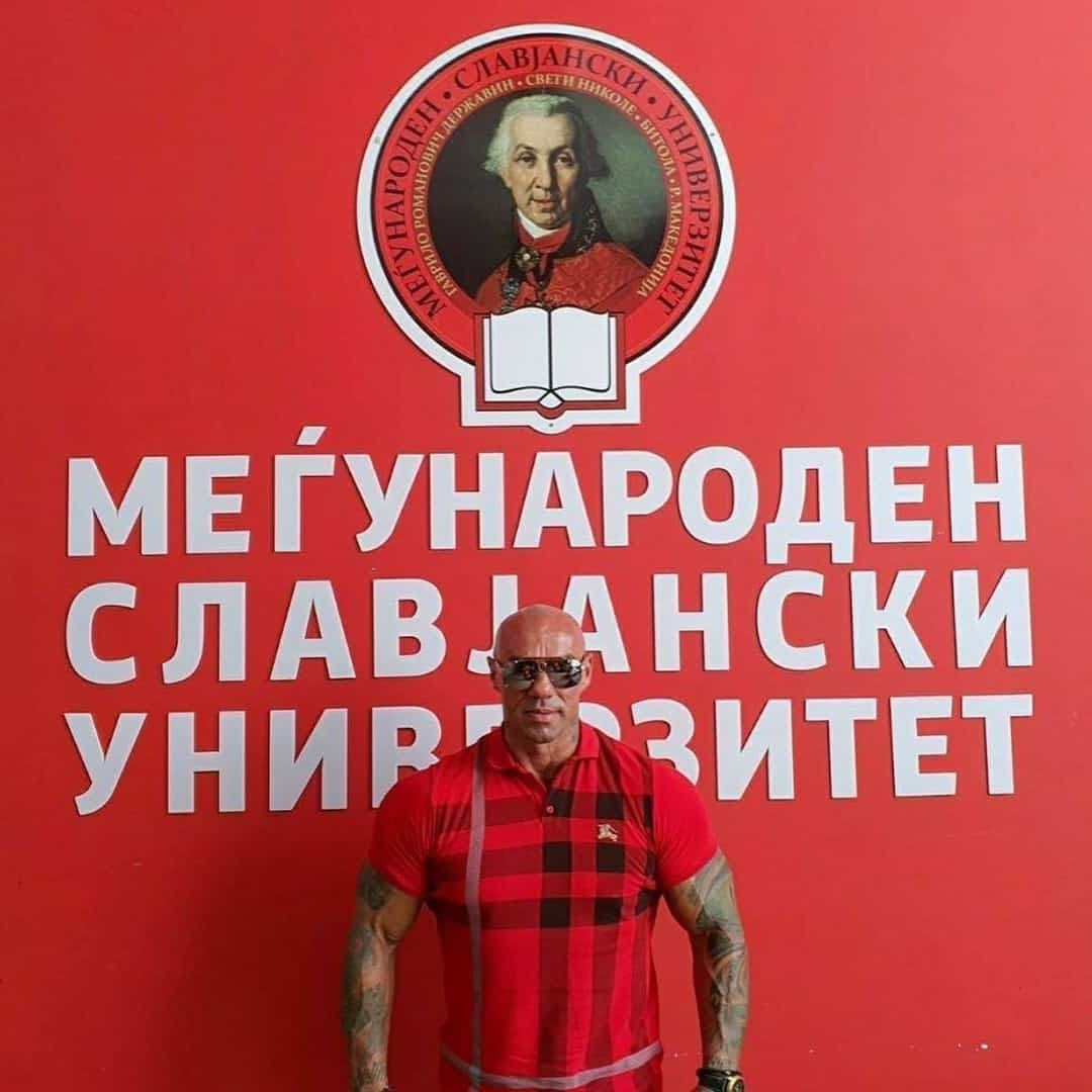 Tose Zafirov in front of a red wall with the logo of the International Slavic University G. R. Derzhavin. He is wearing red t-shirt with black details, and sunglasses on his eyes.